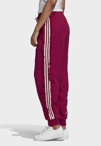 adidas Originals - BELLISTA SPORTS INSPIRED JOGGER PANTS - Tracksuit bottoms - power berry - 2