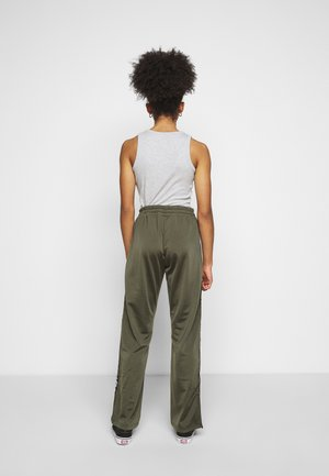 TAOTRACK PANTS OVERLENGTH - Tracksuit bottoms - grape leaf