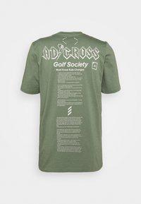 adidas Golf - CROSS - Print T-shirt - natural green - 1