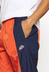 Nike Sportswear - Tracksuit bottoms - mantra orange/obsidian/orange frost - 4
