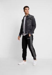 Calvin Klein Jeans - SIDE STRIPE TRACK PANT - Tracksuit bottoms - black - 1