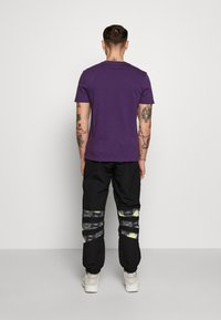 adidas Originals - FOOTBALL GRAPHIC TRACK PANTS - Verryttelyhousut - black - 2