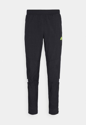 ULTRA PANT - Pantalon de survêtement - black/yellow