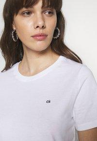 Calvin Klein - SMALL LOGO EMBROIDERED TEE - Jednoduché triko - white - 4