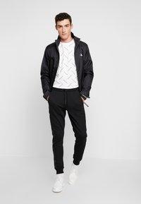 Calvin Klein Jeans - INSTIT TAPE MIX MEDIA PANT - Teplákové kalhoty - black - 1