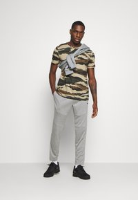 Puma - TRAIN TAPERED PANT - Pantalon de survêtement - medium gray heather
