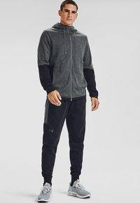 Under Armour - Tracksuit bottoms - black - 0