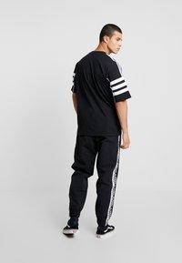 adidas Originals - REVEAL YOUR VOICE - Tracksuit bottoms - black - 2