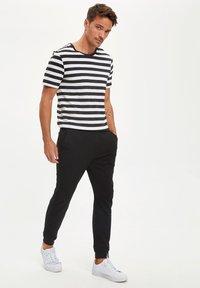 DeFacto - Pantalones deportivos - black - 1