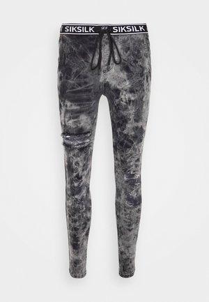 DISTRESSED ELASTICATED - Vaqueros slim fit - bleach black tie dye