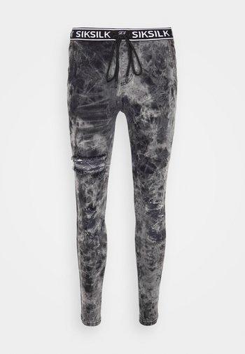 DISTRESSED ELASTICATED - Slim fit jeans - bleach black tie dye