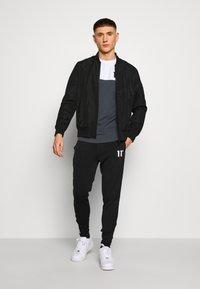 11 DEGREES - TAPED TRACK PANTS - Pantaloni sportivi - black - 1