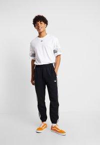adidas Originals - STRIPE PANEL - Tracksuit bottoms - black/white - 1