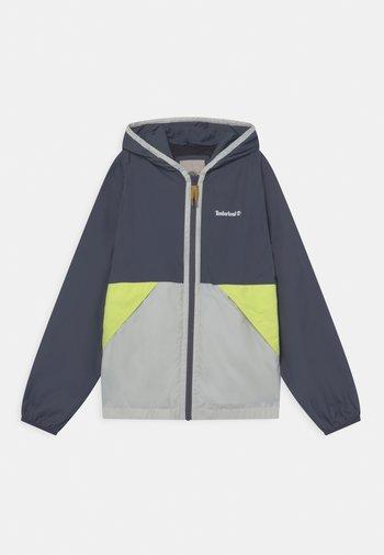 HOODED - Waterproof jacket - stone
