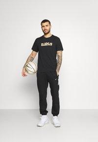 Nike Performance - DRY LOGO TEE - Print T-shirt - black/gold dart - 1