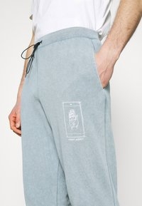 Night Addict - PALM - Tracksuit bottoms - blue
