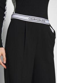 Calvin Klein Jeans - LOGO ELASTIC DRAPEY PANT - Spodnie materiałowe - black - 5