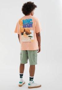 PULL&BEAR - MIT FARBLICH ABGESETZTEM SLOGAN - Print T-shirt - orange - 2