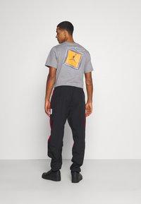 Jordan - Tracksuit bottoms - black/gym red - 2