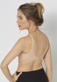 triaction by Triumph - WELLNESS  - Medium support sports bra - neutral beige - 1