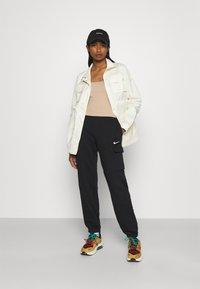Nike Sportswear - CARGO LOOSE - Pantalones deportivos - black - 1