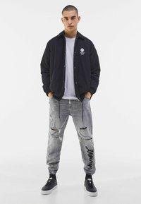 Bershka - MIT PRINT UND ZIERRISSEN  - Jeans Tapered Fit - grey - 1