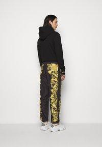 Versace Jeans Couture - PRINT BAROQUE - Tracksuit bottoms - black - 2