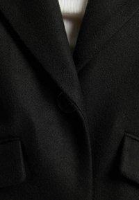 Bershka - MIT FALLENDEN SCHULTERNÄHTEN  - Klasyczny płaszcz - black - 5
