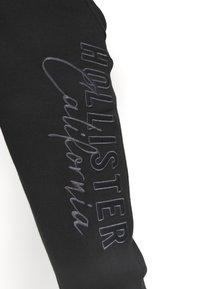 Hollister Co. - HERITAGE TECH - Tracksuit bottoms - black - 3