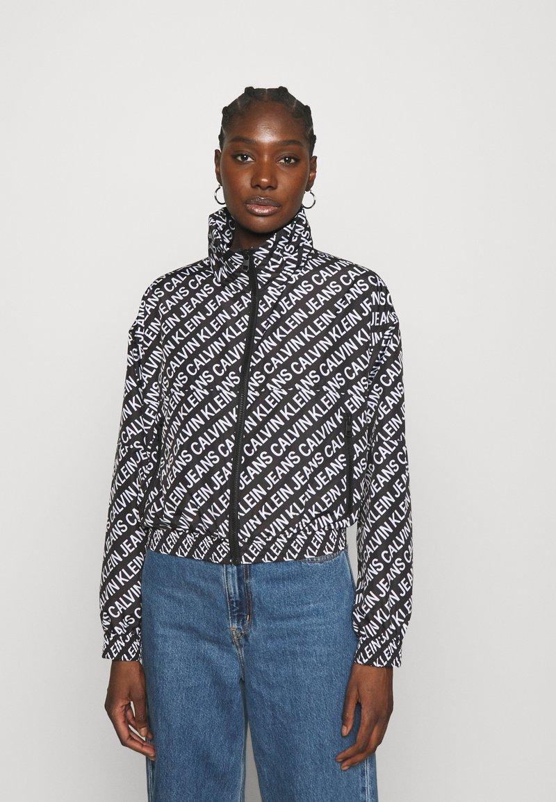 Calvin Klein Jeans - PACKABLE HOOD WINDBREAKER - Summer jacket - black
