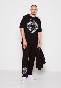 Tommy Hilfiger - ONE PLANET UNISEX - Tracksuit bottoms - black - 3