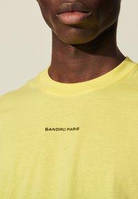 sandro - SOLID TEE UNISEX - Basic T-shirt - jaune citron - 4