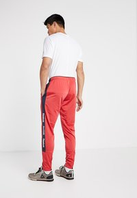 Reebok - TRAINING ESSENTIALS TRACK PANTS - Tracksuit bottoms - red - 2