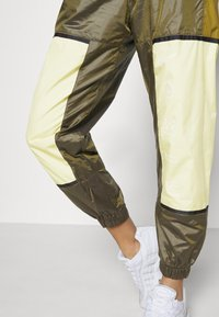 Nike Sportswear - WVN ARCHIVE RMX - Teplákové kalhoty - olive flak/tea tree mist/white - 4