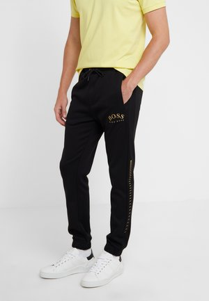 HADIKO WIN - Tracksuit bottoms - black/gold