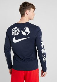 Nike Performance - DRY RUN SEASONAL  - Camiseta de deporte - obsidian/white - 2