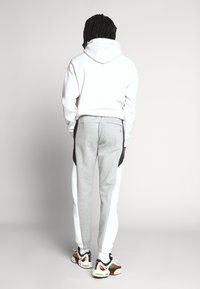 Nike Sportswear - Tracksuit bottoms - dark grey heather/white/black - 2