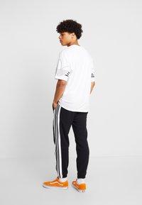 adidas Originals - STRIPE PANEL - Tracksuit bottoms - black/white - 2