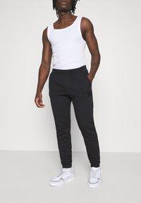 adidas Originals - PANT UNISEX - Tracksuit bottoms - black - 0