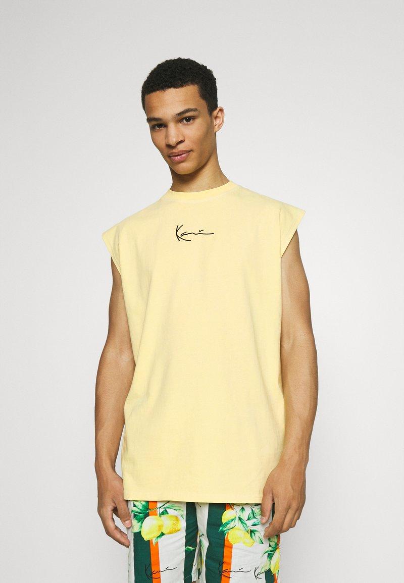 Karl Kani - SMALL SIGNATURE WASHED SLEEVELESS TEE - Triko spotiskem - light yellow