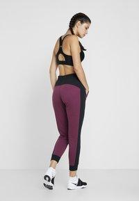 Under Armour - RIVAL GRAPHIC NOVELTY PANT - Spodnie treningowe - level purple/black - 2
