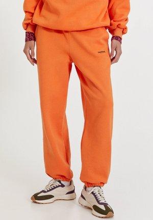 MIT BUNTEM SLOGAN - Tracksuit bottoms - orange