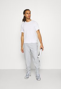 Nike Performance - RUN STRIPE PANT - Tracksuit bottoms - light smoke grey/smoke grey/reflective silver - 1