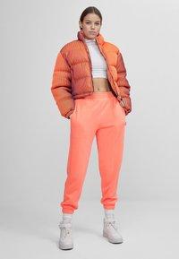 Bershka - LENTICULAR - Tracksuit bottoms - orange - 1