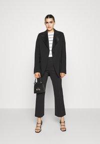 DESIGNERS REMIX - SANSAH FLARED - Trousers - black - 1