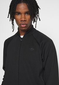 adidas Originals - WARMUP - Training jacket - black/goldmt - 3