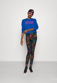 Versace Jeans Couture - Leggings - Trousers - black/multi coloured - 1