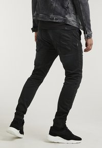 CHASIN' - RESA.L THOR - Trousers - black - 1