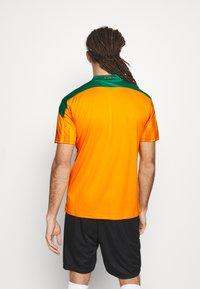 Puma - ELFENBEINKÜSTE FIF HOME SHIRT REPLICA - National team wear - flame orange/pepper green - 2