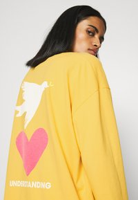 Levi's® - GRAPHIC OVERSIZE TEE - Long sleeved top - dark yellow - 3